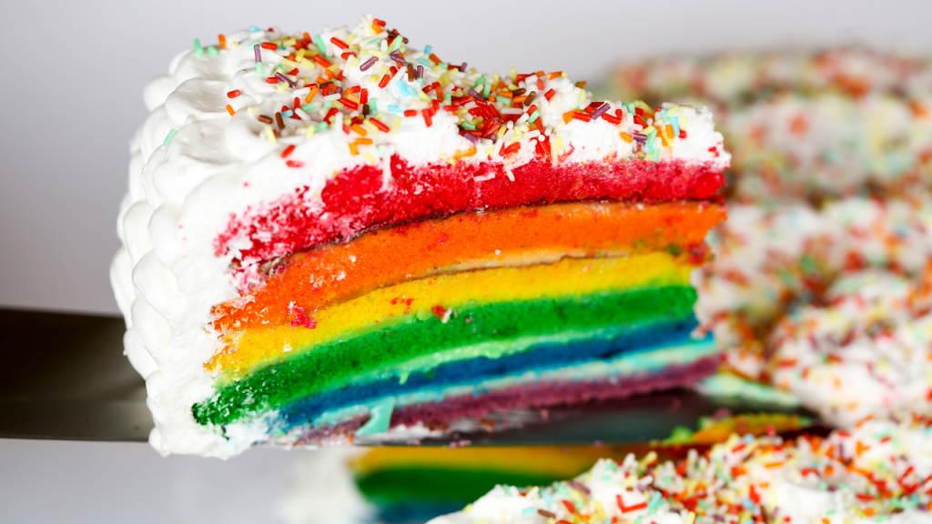 A slice of rainbow layer cake is lifted out of a white-frosted cake covered in sprinkles. Photo.
