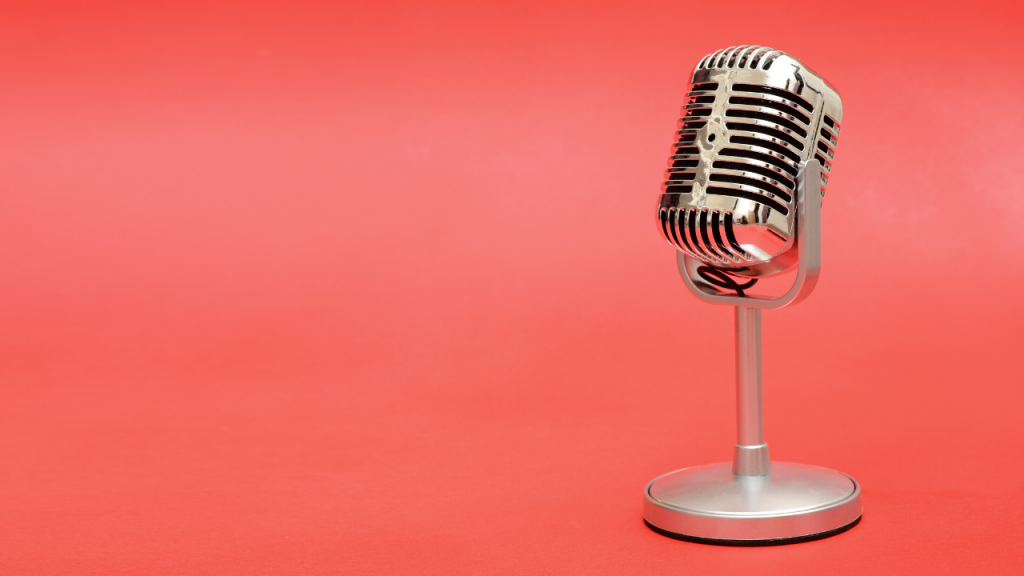 A shiny microphone on a pink background. Photo.