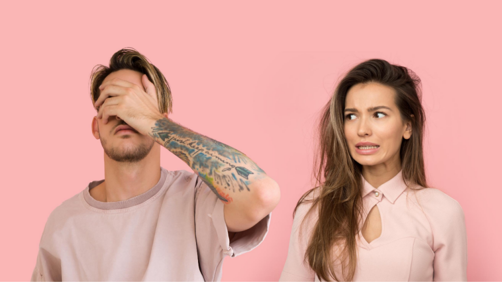 A gender non-confirming amab person in a pink shirt with tattoos on their arms covers their face with their hands in frustration while an afab person makes a face of awkward apology.